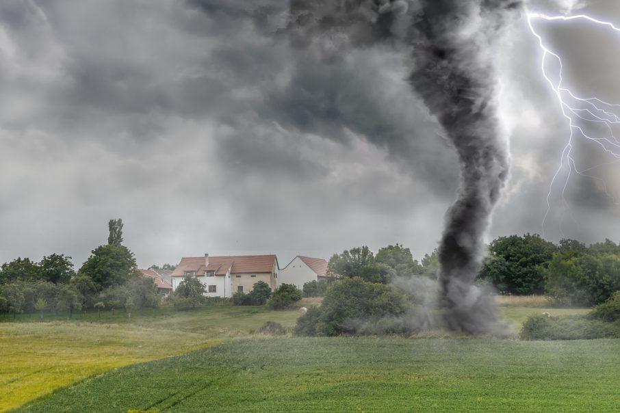 Black,tornado,funnel,and,lightning,over,field,during,thunderstorm